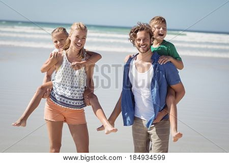 Portrait of happy parents piggybacking their children on shore at beach during sunny day