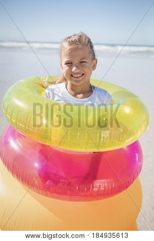 Portrait of girl standing in inflatable rings at beach during sunny day