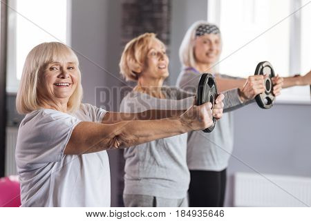 Weight discs. Joyful active retired woman standing with her friends and holding a weight disc while doing a physical exercise
