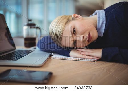 Portrait of tried executive leaning on desk in office