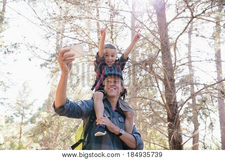 Low angle view of father carrying son on shoulders while taking selfie against trees in forest