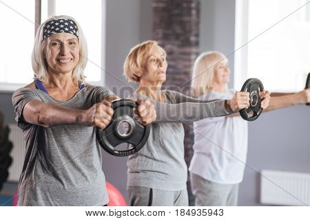 Staying healthy. Joyful senior nice women smiling and exercising with weight discs while having fitness training