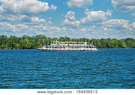 A river pleasure boat sails on the water against the background of green trees