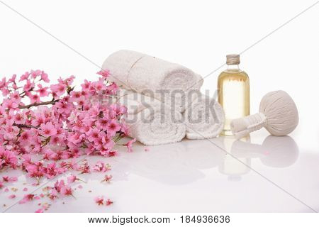 Spa treatment with blooming branch cherry ,ball,towel ,oil on white background