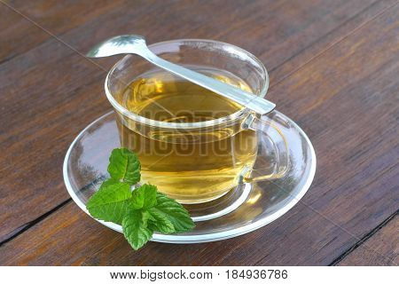 Glass cup of mint tea with tea spoon and mint leaves served outside on a wooden desk