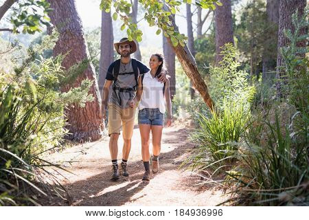 Happy young couple walking with arm around on trail in forest