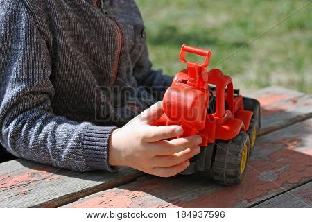 Image of a small child who sits outdoors at the old table with wooden surface. A child plays with a red toy construction vehicles.