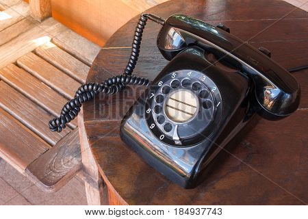 Old Black Phone With Dust, Circle Dialpad And Scratches On Wooden Retro Desk. Vintage Desk Telephone