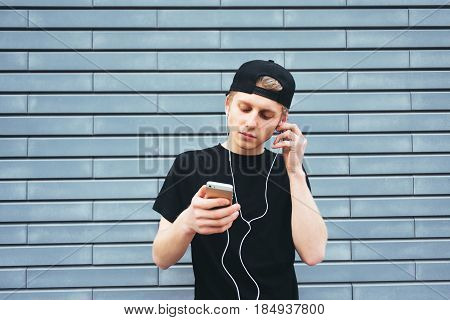 Beautiful young man in a cap and a black T-shirt gets listening to music on headphones with your phone. Student listening to music on a background of blue wall
