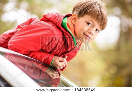 Close-up portrait of cute little boy standing in open car sunroof and looking at camera