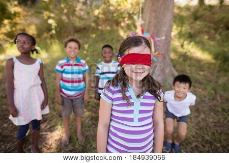 Friends looking at blindfolded girl standing on grassy field in forest