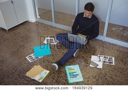 High angle view of young businessman sitting on floor while working in creative office