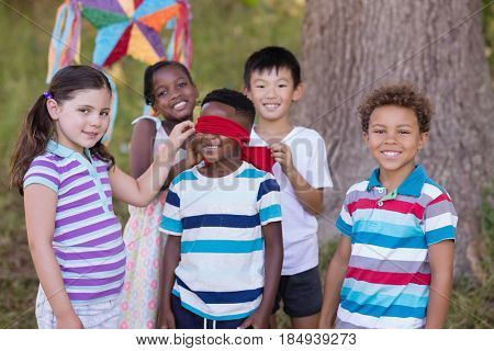 Portrait of friends standing around blindfolded boy at campsite