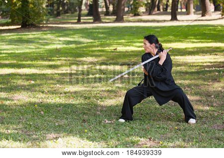 Martial Arts Sword Mastermartial Arts Training Outdoors. Green Background. Color Image