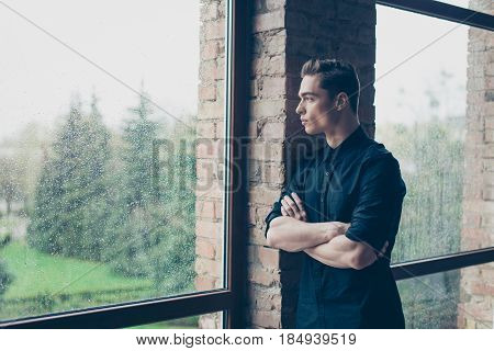Young Cute Dreamy Boy Is Looking Far Away In The Window. He Is In Black Outfit, His Arms Are Crossed