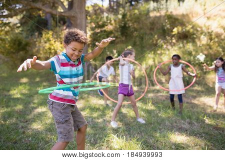 Group of friends enjoying with hula hoops on grassy field at campsite