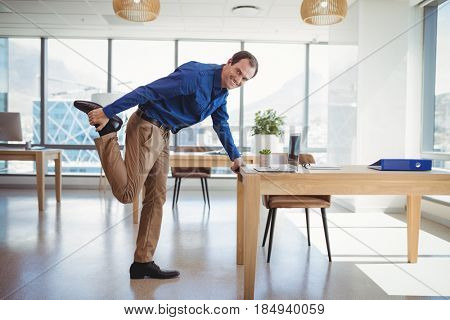 Portrait of smiling executive exercising in office