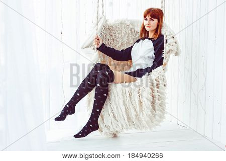 Young carefree girl swinging on a wooden swing and looking at the camera