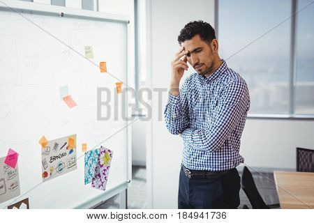 Tensed executive standing near whiteboard in office