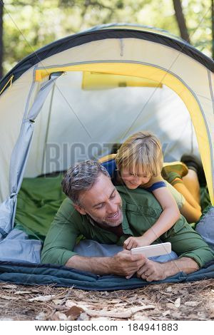 Happy father and son enjoying while using mobile phone in tent at campsite