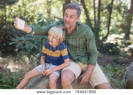 Mischief father and son sticking out tongue while taking selfie in forest