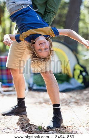 Playful father holding son upside down at campsite