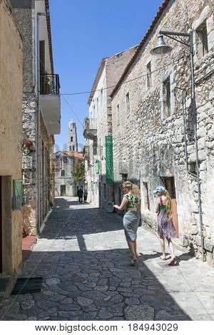areopoli, greece, 15 april 2017: tourists walk the ancient streets of areopolis in greece on mani peninsula of peloponnese with old church tower in the background