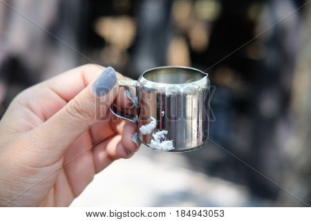 Stainless steel mini cup in hand with blur background