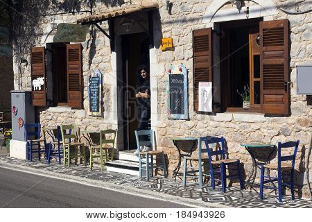 kardamili, Greece, 25 april 2017: waitress waits for customers in open door of old tavern in Mani village of cardamili on peloponnese in greece on sunny spring day