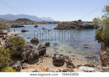 beautiful beach of Stoupa in greece on sunny day in spring on peloponnese with lonely figure and fresh green spring vegetation