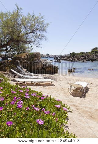 beautiful beach of Stoupa in greece on sunny day in spring on peloponnese with flowers and sunbeds and village in the background