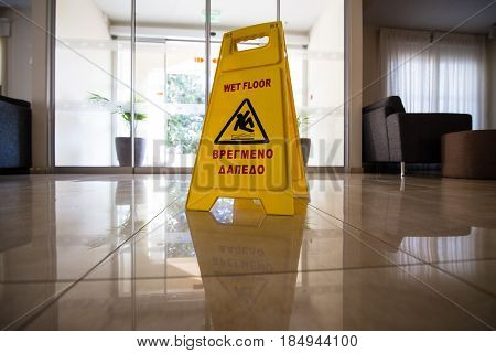 Sign showing warning of caution wet floor on the wet tile floor. The hotel