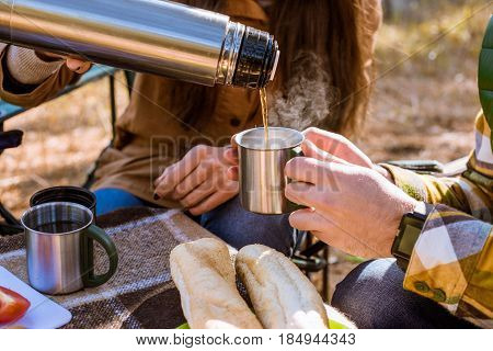 Woman Pouring Tea From Thermos
