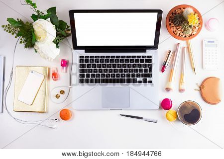 Feminine workspace with modern laptop, coffee and flowers, top view and copy space on empty screen