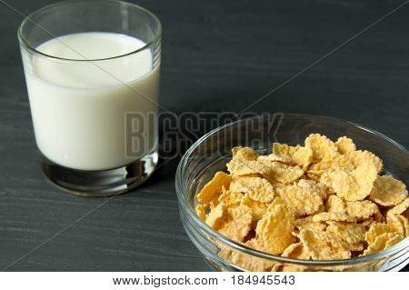 Corn Flakes On Glass Bowl And Glass Of Milk Isolated On Grey Surface