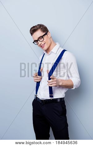 Young Handsome Macho In Formal Wear With Suspenders And In Glasses Is Smiling And Pointing With Fing