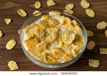 Corn Flakes In A Glass Bowl With Milk On A Wooden Surface