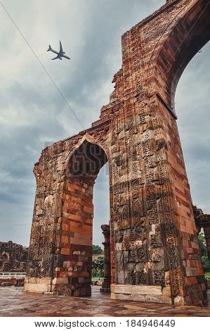 Airplane in sky above Qutb Minar Complex in New Delhi, India