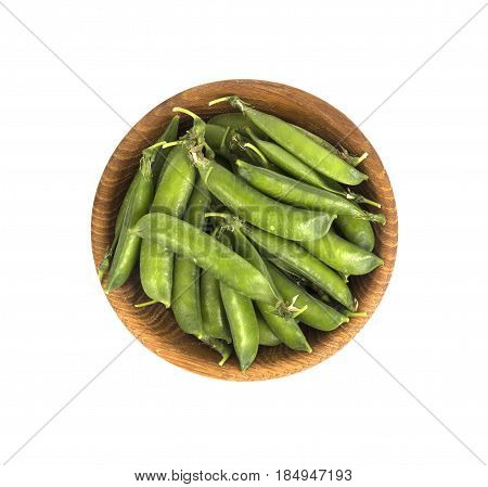 Green peas in wooden bowl on a white background