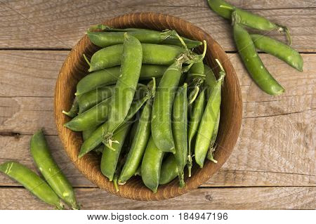 Green peas in wooden bowl on a wooden background
