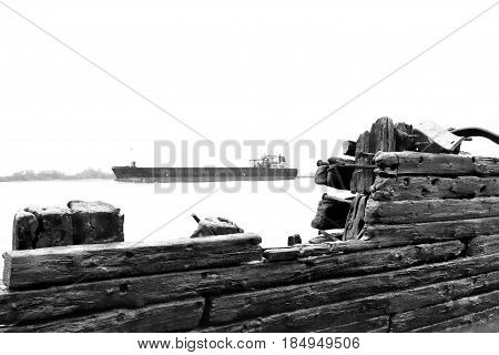 Old, stranded shipwreck on the beach with weathered wood. Ancient ship wreckage and container ship. Beach scene. Freight shipping, Hamburg.