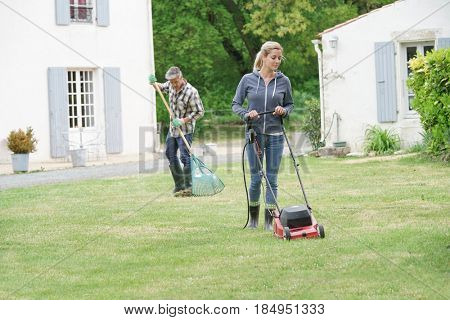 Woman in garden mowing the lawn