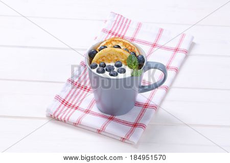 cup of american pancakes with white yogurt and fresh blueberries on checkered dishtowel