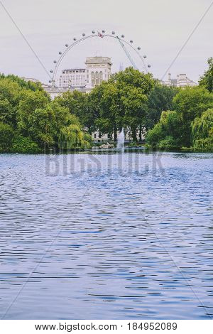 LONDON UNITED KINGDOM - August 12 2015: View over Buckingham Palace and the London Eye from the Blue Bridge over St James Park lake