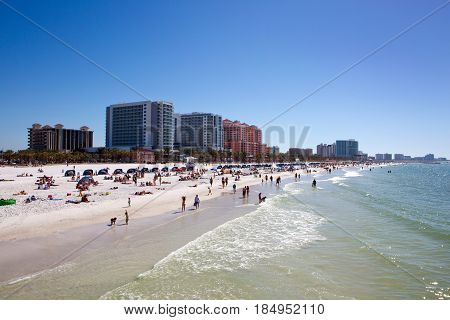 Tourists swim and play at the beach on Clearwater Beach Florida with luxury hotels in the background.