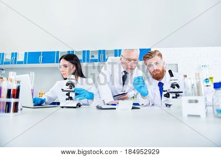 Science And Teamwork Concept - A Group Of Three Scientists Are Making Research In Clinical Laborator