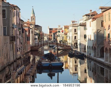 Chioggia, Italy.  A canal with a bridge, the palaces are reflected in the water