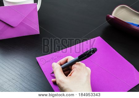 Female writing a pen pal letter note at a desk