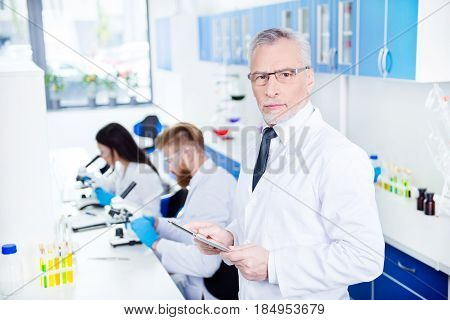 Laboratory Work Of Three. Close Up Portrait Of Professor In Formal Wear And Special Labcoat In Glass