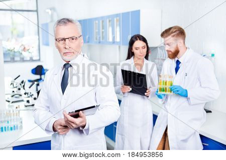 Teamwork In Lab. Close Up Focused Portrait Of Professor In Lab Coat And Glasses Holding Tablet And L
